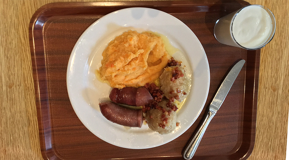 a plate of raspeball, sausage, sweed mash toppet with bacon