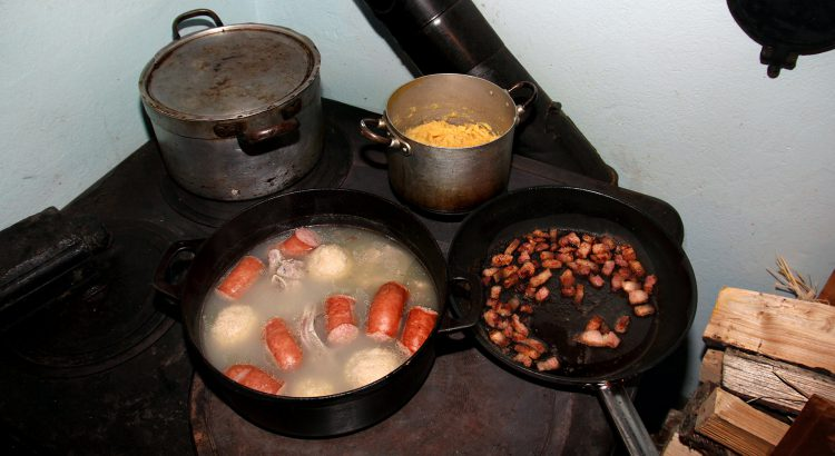 Cooking salted meat, raspeball, sausage, sweed mash on an old wooden stove.