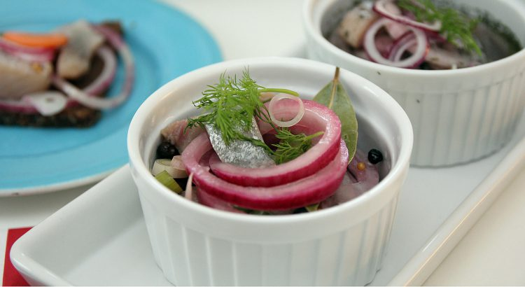 Picture of pickled herring pickled in a glass jar.