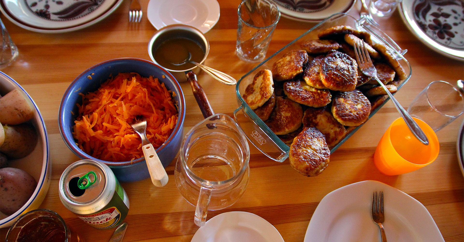 Show a table full of plates with fish cakes, potatos and carot.