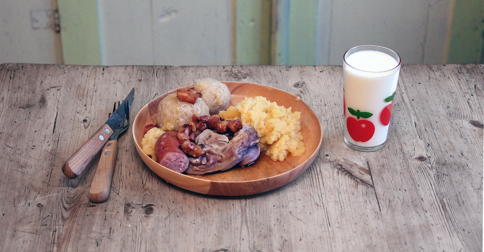 Picture of a plate of raspeball, sausage, sweed mash toppet with bacon served on an old wooden table in an old norwegian wooden hut.